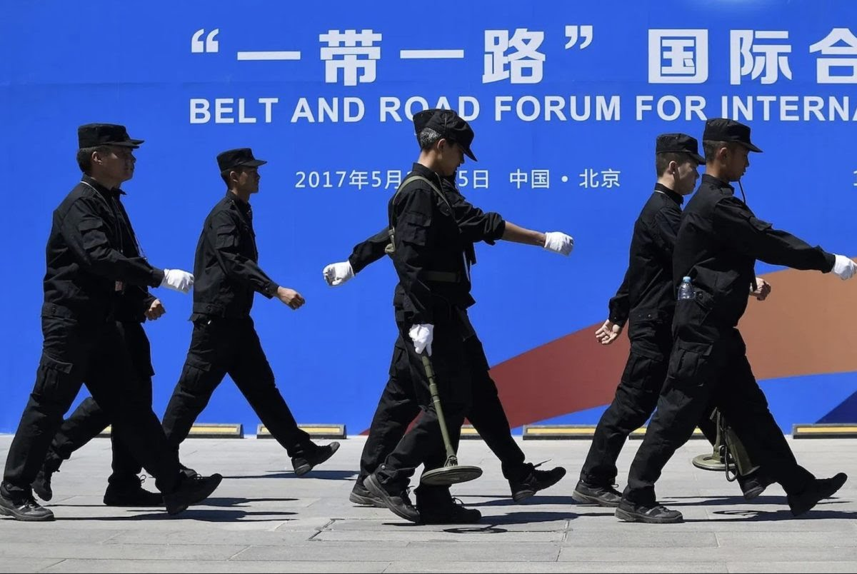Security guards walk past a billboard for the Belt and Road Forum for International Cooperation in Beijing on May 13, 2017